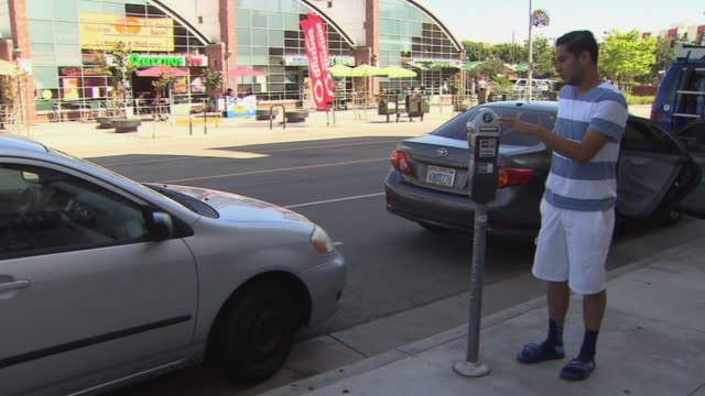 man pays for parking using parking meter on july 31 2013 in los angeles california - parking ticket stock videos & royalty-free footage