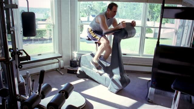 MS, man pedaling on exercise bike in gym, USA, Pennsylvania, Solebury