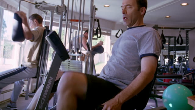 ms, man pedaling on exercise bike then rubbing knee, usa, pennsylvania, solebury, - exercise equipment stock videos and b-roll footage