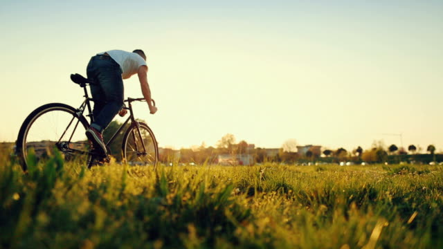 Man pedalling his bicycle on on a field