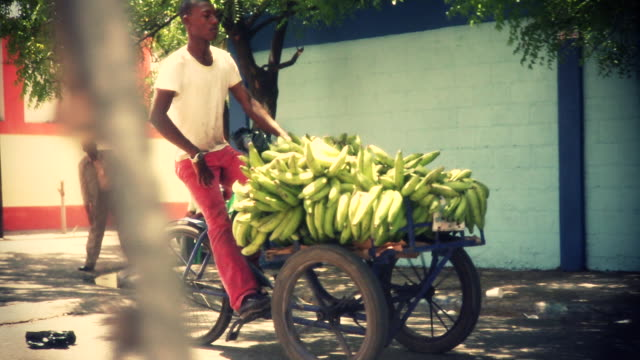 a man pedals a bicycle with a basket of bananas through the dominican republic. - ドミニカ共和国点の映像素材/bロール
