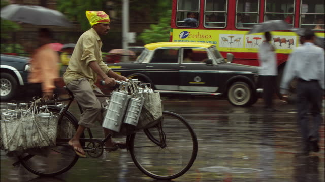 a man pedals his bike loaded with supplies along a busy, rainy street. available in hd. - taxi stock videos & royalty-free footage