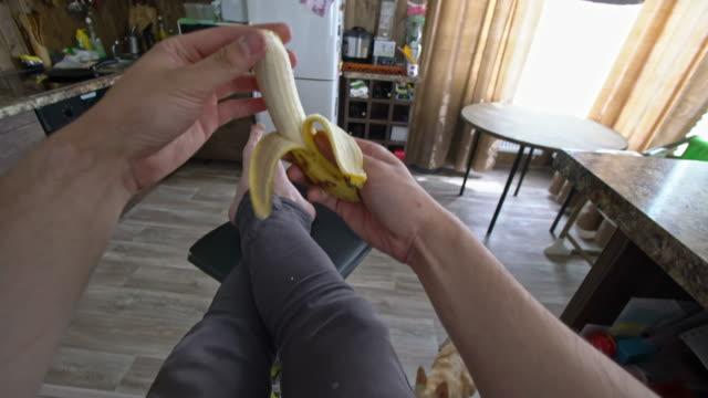 POV of man peeling and eating banana