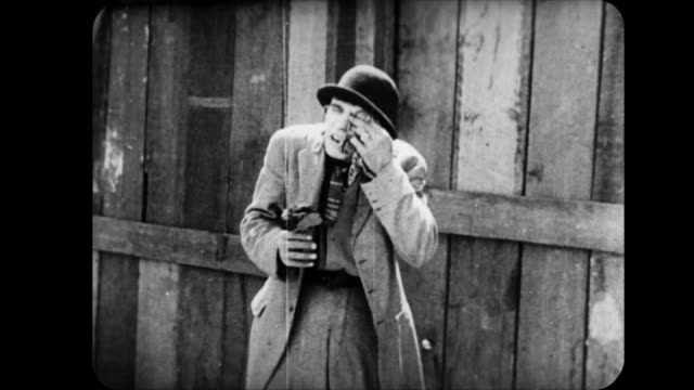 1914 man peeps though fence hole and gets painted eye - 1914 stock videos & royalty-free footage