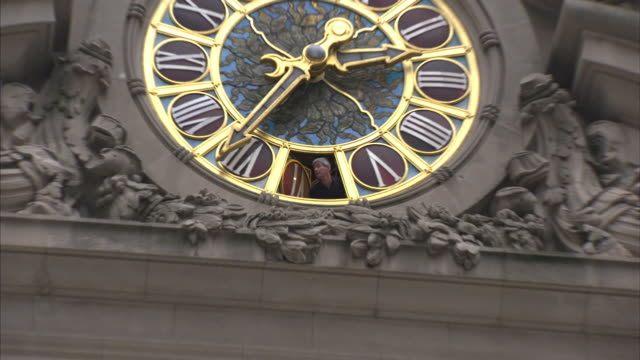 a man peers out of a roman numeral on a large clock at grand central station. - roman numeral stock videos & royalty-free footage