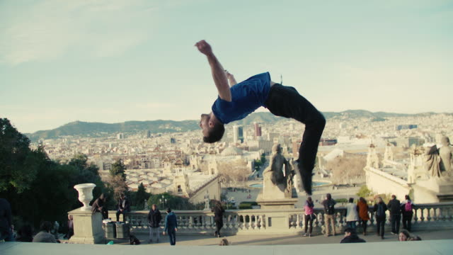 vídeos de stock e filmes b-roll de man performing a backflip with barcelona on the background - plano geral