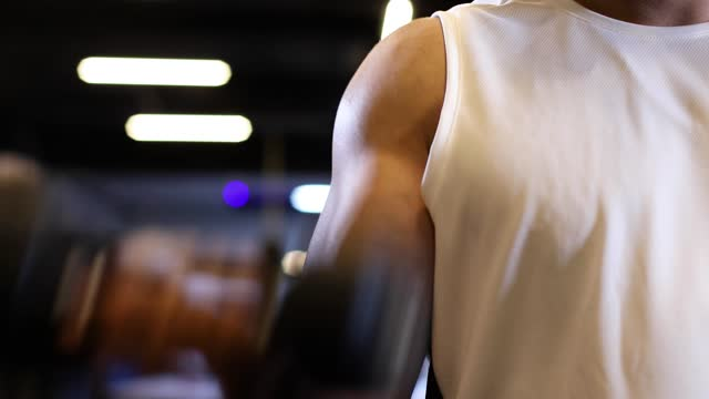 man performing a biceps curl with a dumbbell in a gym. - arm curl stock videos & royalty-free footage
