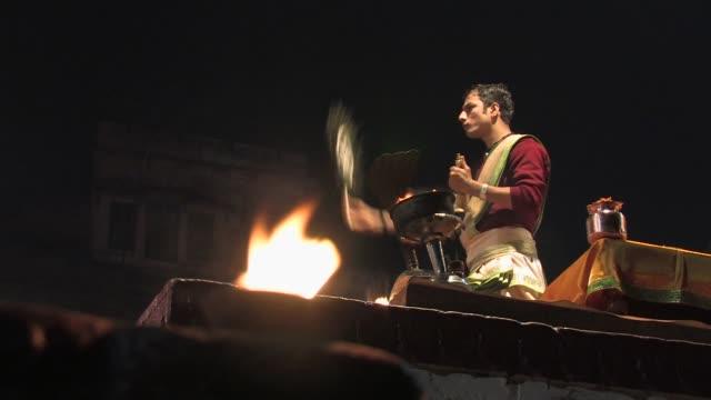 ms, selective focus, la, man performing aarti ritual at night, varanasi, uttar pradesh, india - hand fan stock videos & royalty-free footage