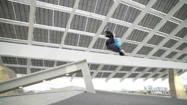 man performing backflip parkour beneath solar panels at barcelona - sport concepts - パフォーマンス点の映像素材/bロール