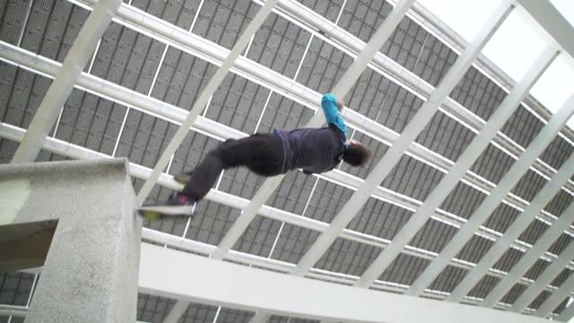 Man performing backflip parkour beneath solar panels at Barcelona - Sport Concepts