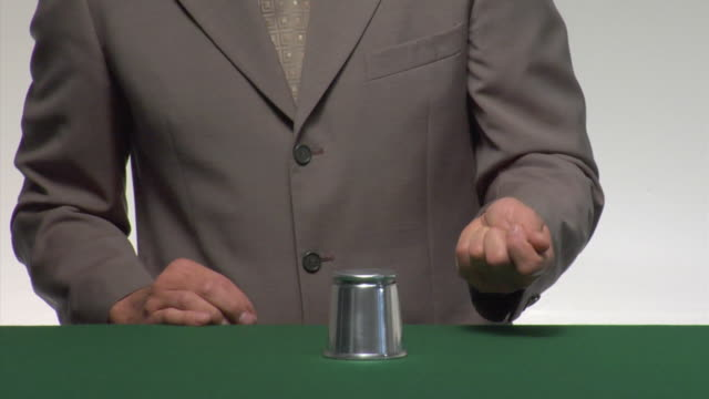 ms man performing ball and cup trick on green table - magician stock videos & royalty-free footage