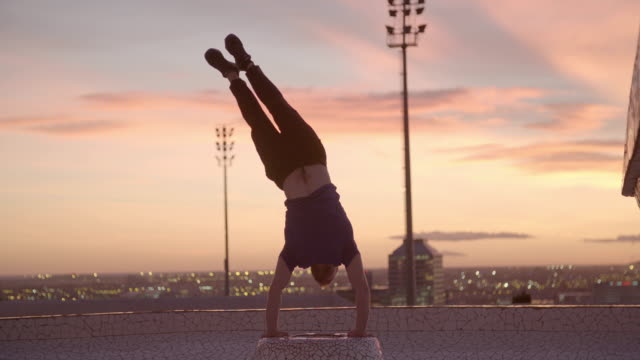 man performing handstand at sunset - upside down stock videos & royalty-free footage