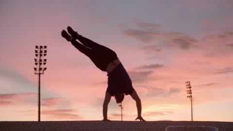 man performing handstand at sunset - erwachsene person stock-videos und b-roll-filmmaterial
