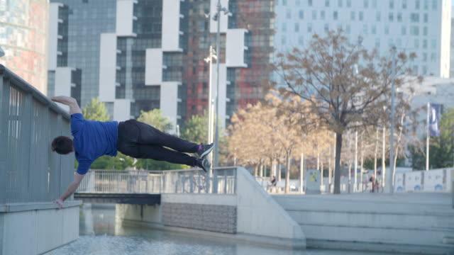 Man performing human flag parkour calisthenics outdoors - Sport Concepts