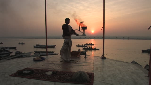 WS, Man performing Puja ritual by Ganges river at sunrise, Varanasi, Uttar Pradesh, India