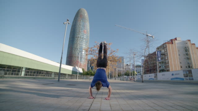 Man performing several handstand backflips in Agbar Tower square Barcelona - Sport Concepts