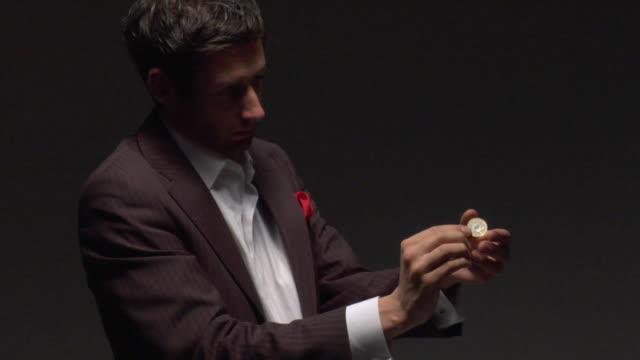 ms man performing tricks with coin - 手品師点の映像素材/bロール
