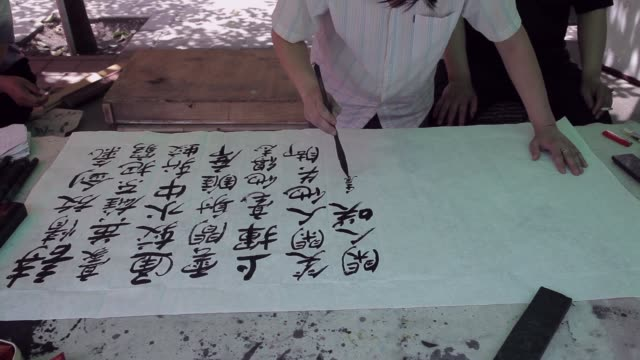 a man performs calligraphy in a roadside stall in china. - chinese script stock videos & royalty-free footage