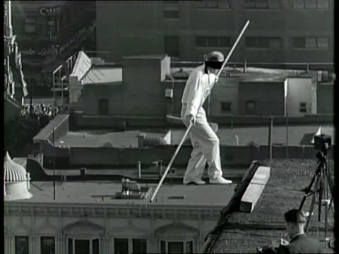 man performs gymnastics on a tightrope over la / - akrobat stock-videos und b-roll-filmmaterial