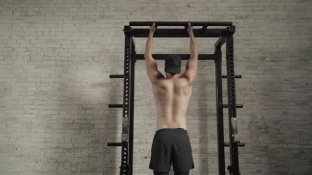 Man performs pullups with squat rack