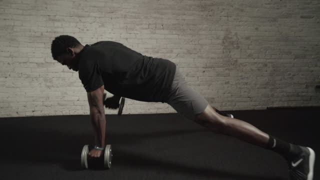 Man performs resistance training with dumbbells
