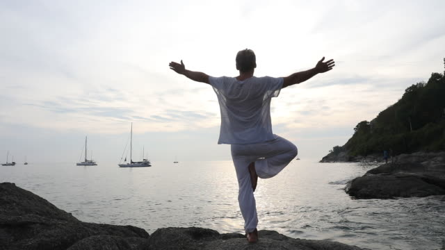 man performs yoga moves on coastal rock slab - one man only stock videos & royalty-free footage