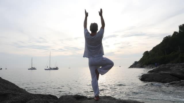 vídeos de stock, filmes e b-roll de homem executa movimentos de ioga na laje de pedra costeiras - de braço levantado