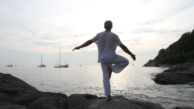 Man performs yoga moves on coastal rock slab