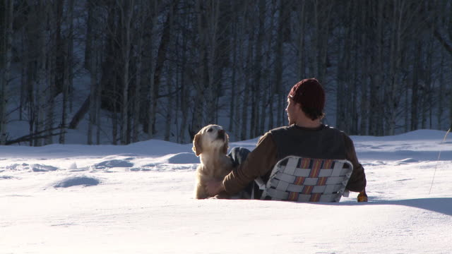 Man petting golden retriever and drinking a beer while sitting in lawn chair out in the snow / Ketchum, Idaho, United States