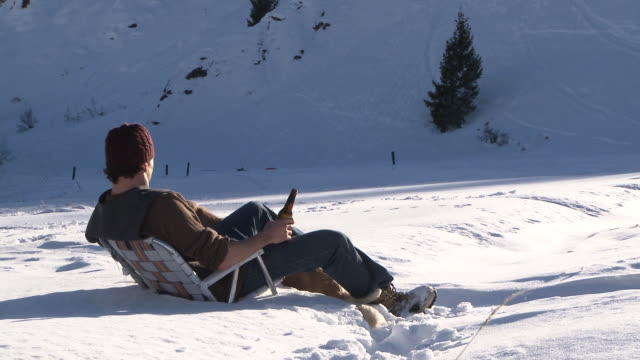 stockvideo's en b-roll-footage met man petting golden retriever and drinking a beer while sitting in lawn chair out in the snow / ketchum, idaho, united states - beer alcohol