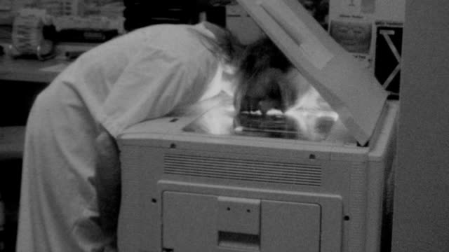 stockvideo's en b-roll-footage met a man photocopies his face repeatedly / photocopying face on november 01 1989 in los angeles california - kopiëren