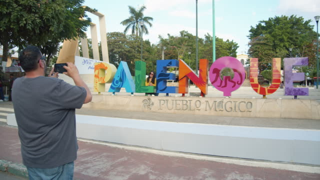 man photographing a woman posing at a colorful landmark sign in palenque, mexico - kunst, kultur und unterhaltung stock-videos und b-roll-filmmaterial