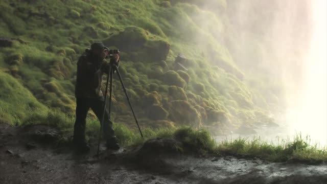 man photographing behind seljalandsfoss waterfall. editorial use only. - fotograf stock-videos und b-roll-filmmaterial