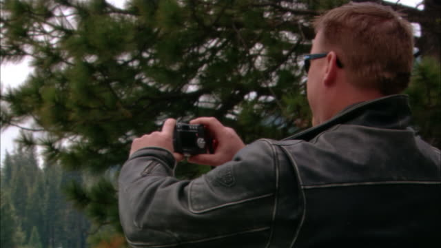 vídeos de stock e filmes b-roll de ms pan man photographing biker friends in sierra national forest / fresno county, california, usa - rasto de movimento