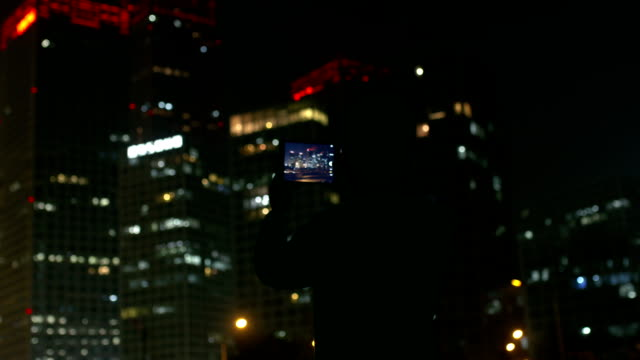 Man photographing city night using tablet