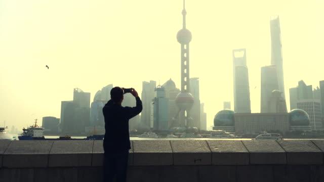 vídeos de stock e filmes b-roll de man photographing city skyline with mobile phone - fotografando