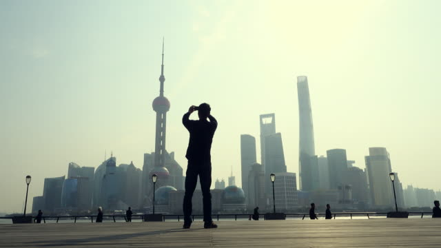 Man photographing city skyline with mobile phone