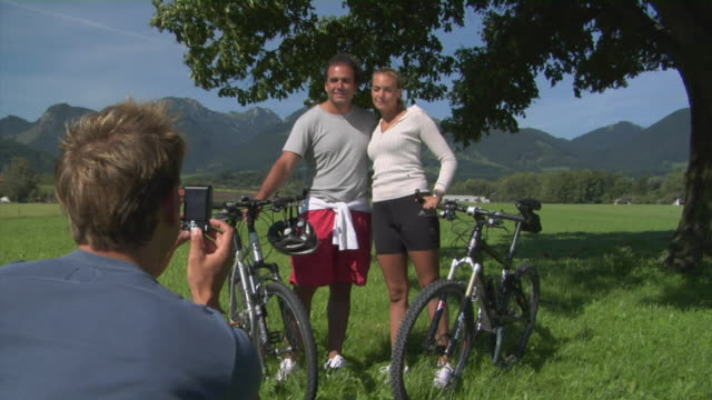 MS Man photographing couple with bicycles in Alpine landscape, Bavaria, Germany