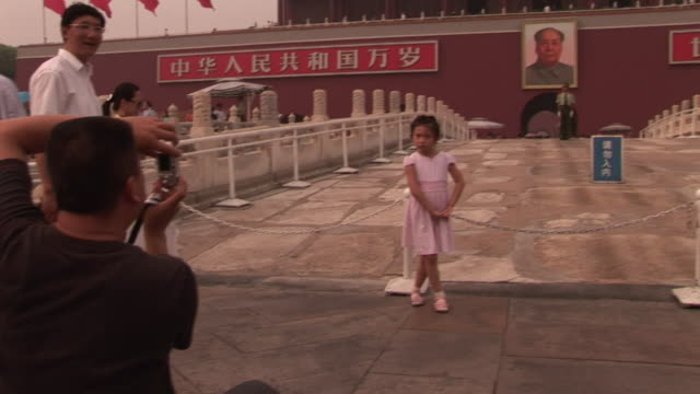 ms, man photographing daughter (6-7) on front of gate of heavenly peace, tiananmen square, soldiers matching in foreground, beijing, china - tiananmen gate of heavenly peace stock videos & royalty-free footage