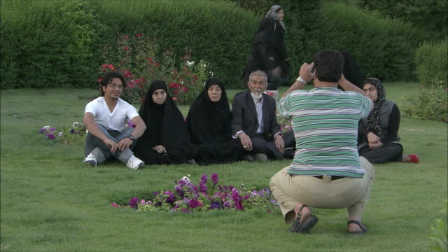 ms man photographing family sitting on lawn, isfahan, iran - burka stock videos and b-roll footage