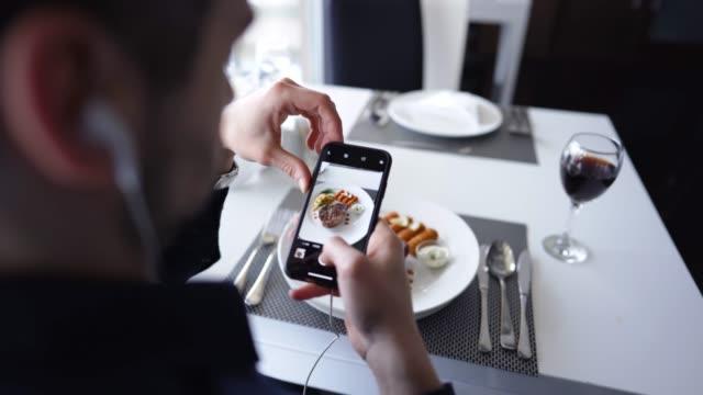 vidéos et rushes de homme photographiant la nourriture sur la pause de déjeuner - influenceur