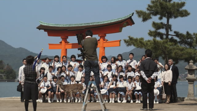 WS Man photographing group of schoolchildren in front of Torii gate at Itsukushima Shrine, Miyajima Island, Japan
