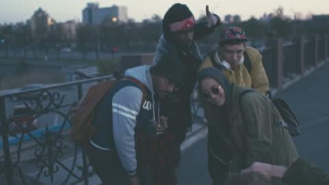 vidéos et rushes de man photographing multiethnic friends in street style clothing - a la mode