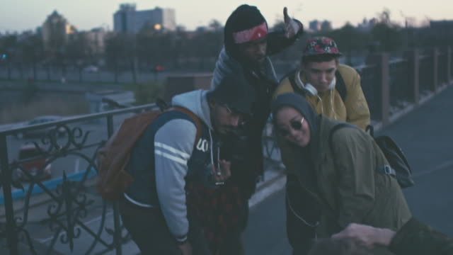 vídeos de stock e filmes b-roll de man photographing multiethnic friends in street style clothing - cultura jovem