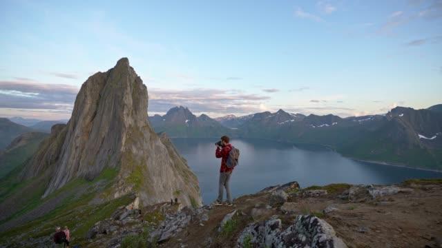 vídeos de stock, filmes e b-roll de homem fotografando montanha segla na ilha senja - escapismo