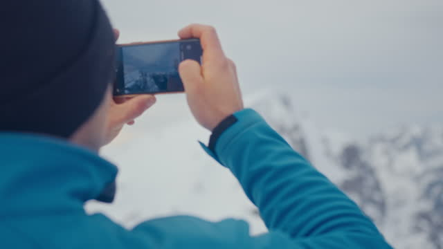 vídeos y material grabado en eventos de stock de hombre fotografiando montaña nevada usando teléfono móvil - nevosa