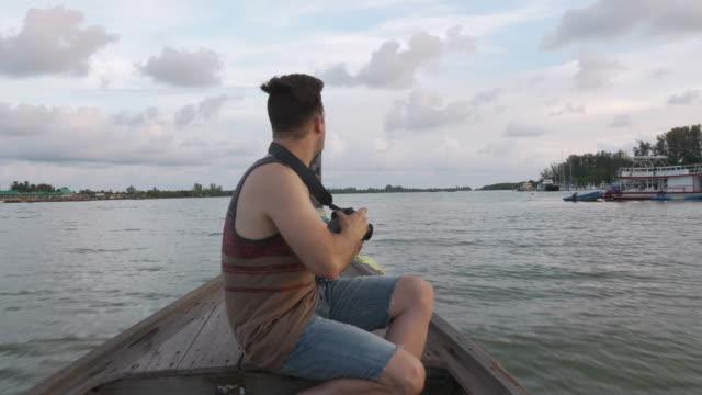 4K UHD: Man fotograferen van de zonsondergang vanaf boot boog