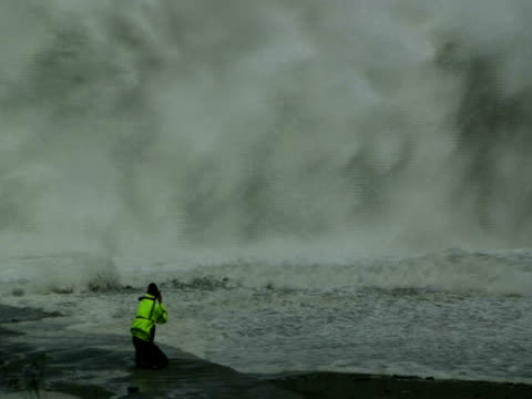 man photographing then fleeing huge storm waves on beach; typhoon jangmi, taiwan, 28th september 2008 (with audio) - runaway stock videos & royalty-free footage