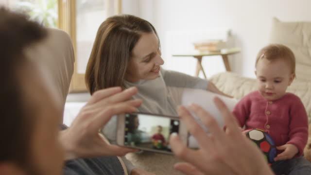vídeos y material grabado en eventos de stock de hombre fotografiando mujer y bebé con teléfono inteligente - sms