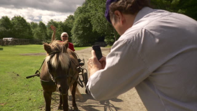 ms man photographing woman sitting on horse drawn carriage and waving / stowe, vermont, usa - stowe vermont stock videos & royalty-free footage